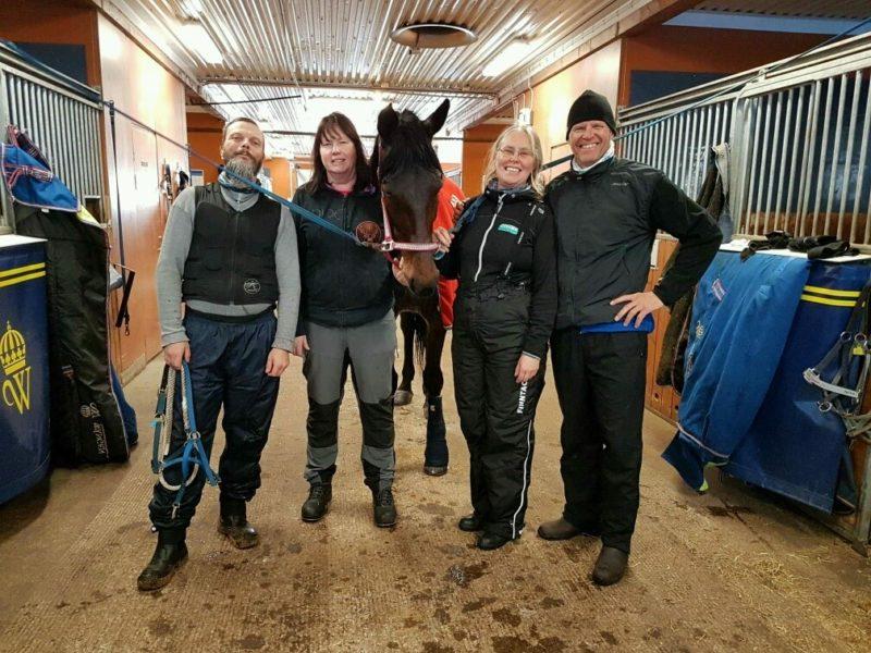 Kursdeltagare på hästskötarkursen står uppställda med glada leenden, två på varje sida om en travhäst som står uppställd på stallgången