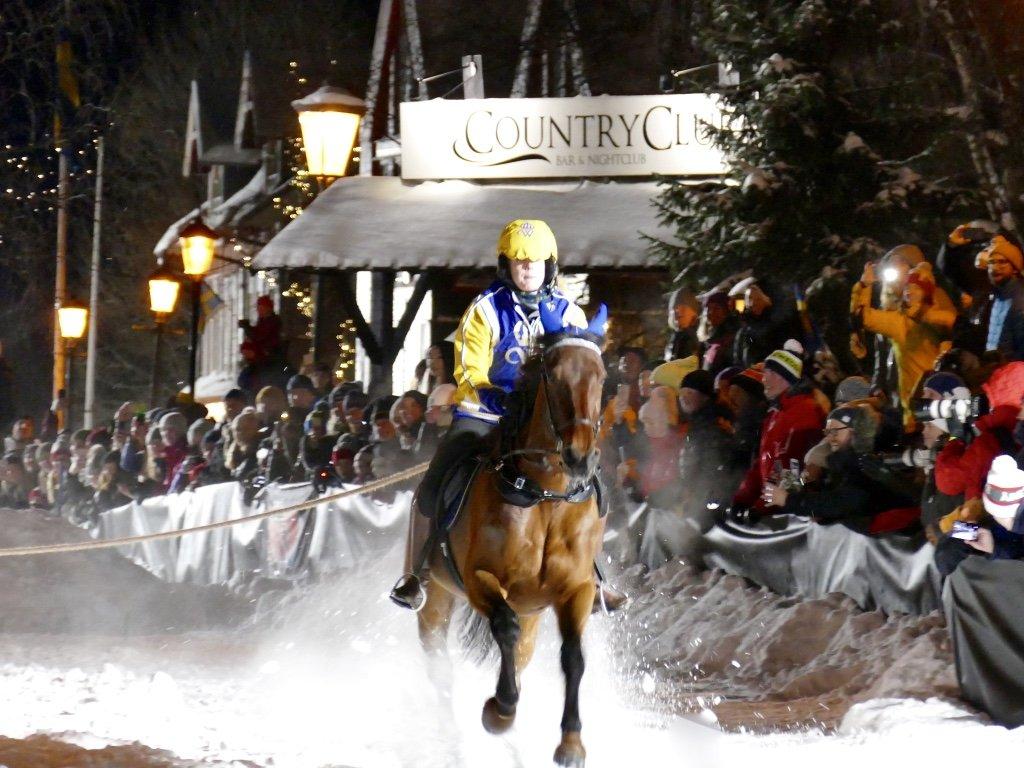 Varmblodshäst galopperar så snön ryker, ryttare bär Wångens gula och blå kläder. I bakgrunden syns publik till skijoring-tävling och skylt med texten Country Club.