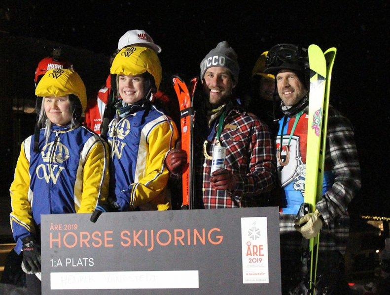 Skidåkare på prispall håller upp sina skidor och de stora checkar de fått. Bredvid syns ryttarna i skijoring-tävlingen. Elever och studenter från Wången i gula och blå kläder.