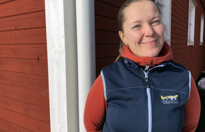 Kvinna i röd tröja och blå väst med Svensk Travsports logotyp på. Hon står och kisar mot solen och i bakgrunden syns en panelad röd stallvägg och en vit knut med stuprör