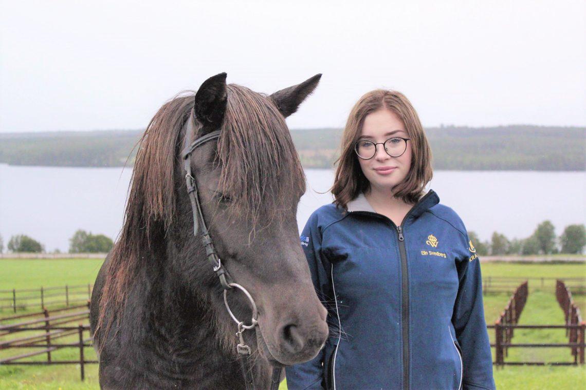 Svart islandshäst i träns bredvid elev. Eleven har mörkt pageklippt hår, runda glasögon och jacka med Wångens emblem. I bakgrunden syns hagar och Alsensjön