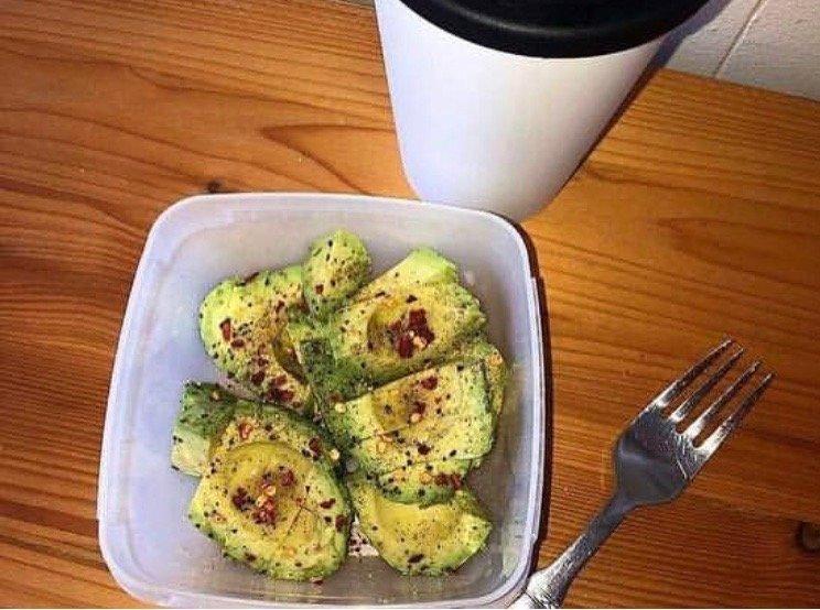 Matlåda med kryddade avokadohalvor. Bredvid syns en gaffel och en pappmugg med kaffe