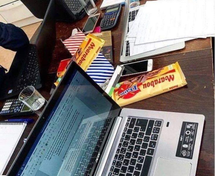 En uppslagen laptop på ett skrivbord. Bredvid ligger en Marabou chokladkaka och papper och miniräknare