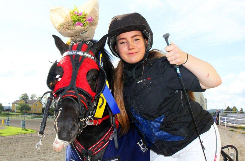 Svart ponny med röd huva har en blombukett över huvudet för att kusken står brevid och håller buketten och hästen i ena handen och gör tummen upp med andra handen som också håller i körspöt