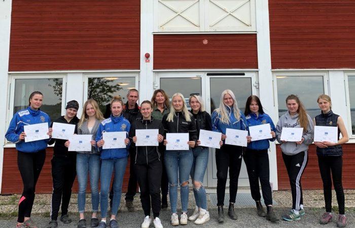 Grupp av gymnasieelever framför skolbyggnad håller sitt EQUES-diplom framför sig