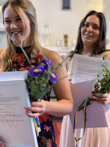 Två leende studenter med blomsterkvastar i händerna.