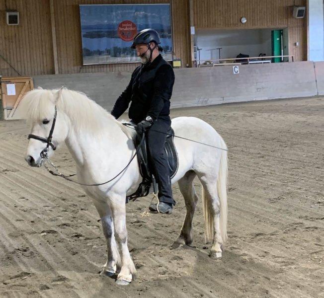 Guðmundur Einarsson på sin vita islandshäst i Wångens ridhus