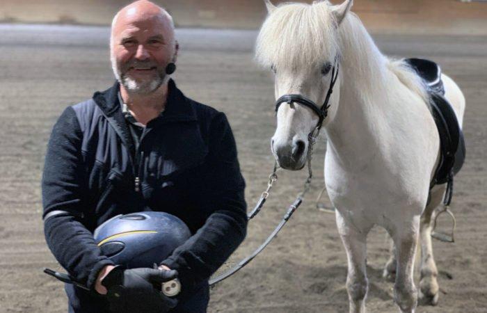 Man med mikrofonheadset ler mot kameran. Han håller hjälmen i handen och tyglarna till en vit häst som står bakom honom