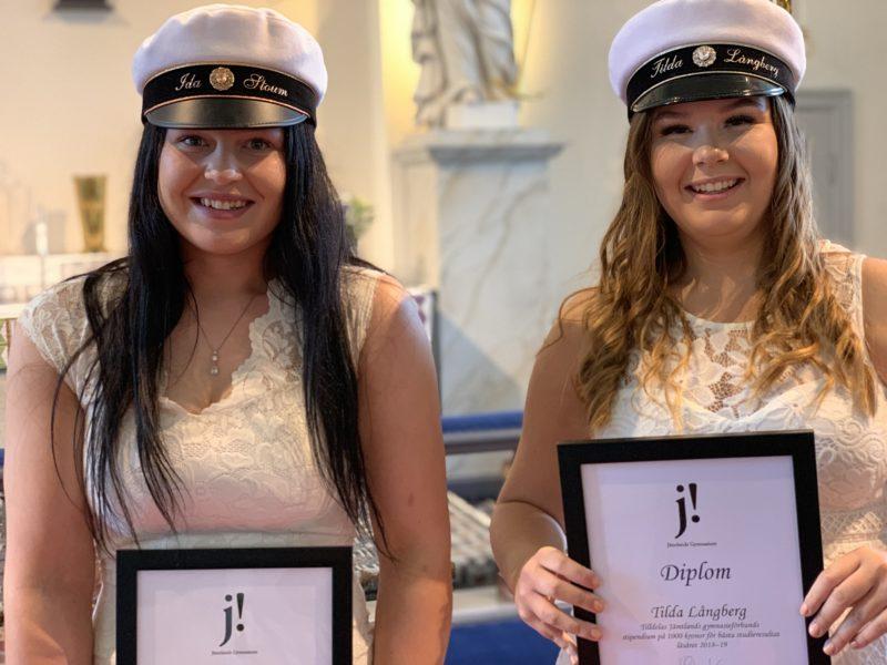 Två flickor med studentmössor och vita klänningar håller varsitt inramat diplom framför sig i kyrkan