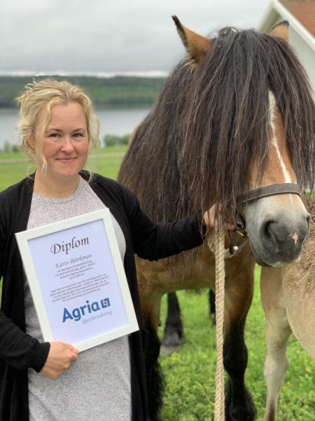 Blond kvinna med diplom i handen håller i en nordsvensk häst. brevid hästen skymtar delar av ett föl