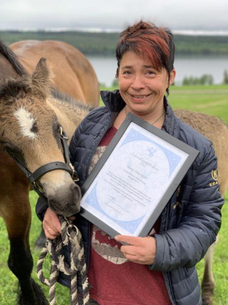 Glad kvinna håller i diplom och nordsvenskt föl