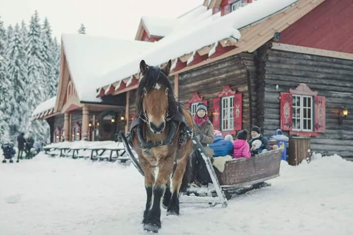 Hästdragen släde framför stort timrat hus som har röda fönsterluckor. Marken är täckt med snö