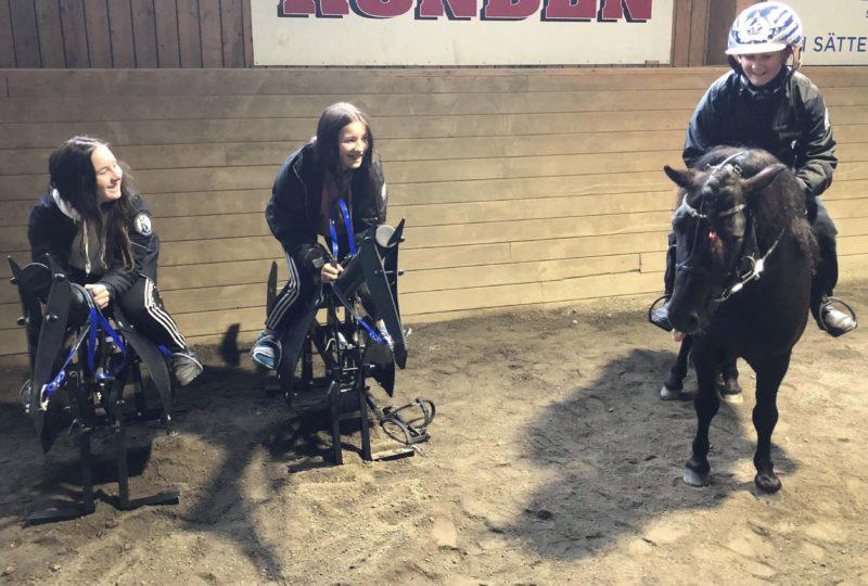 Två deltagare på varsin stålhäst i ridhuset, en tredje deltagare sitter i montésits på sin egen ponny.