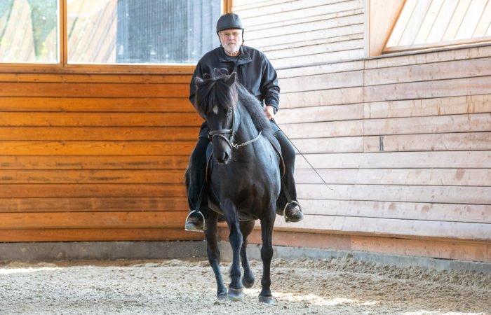 Eyjolfur Isolfsson rider en svart islandshäst i ett ridhus