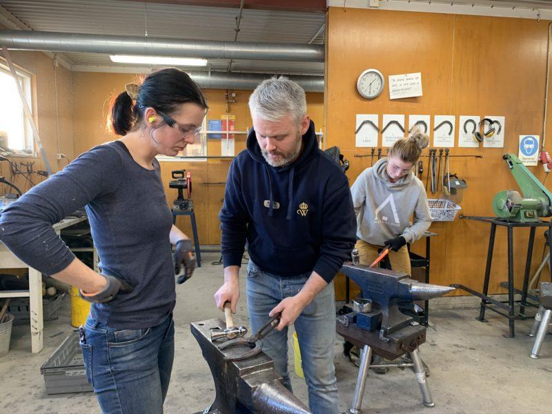 Två personer står på varsin sida om ett städ. Ovanpå städet ligger en hästsko. Läraren håller i en hammare. I bakgrunden syns en annan elev.