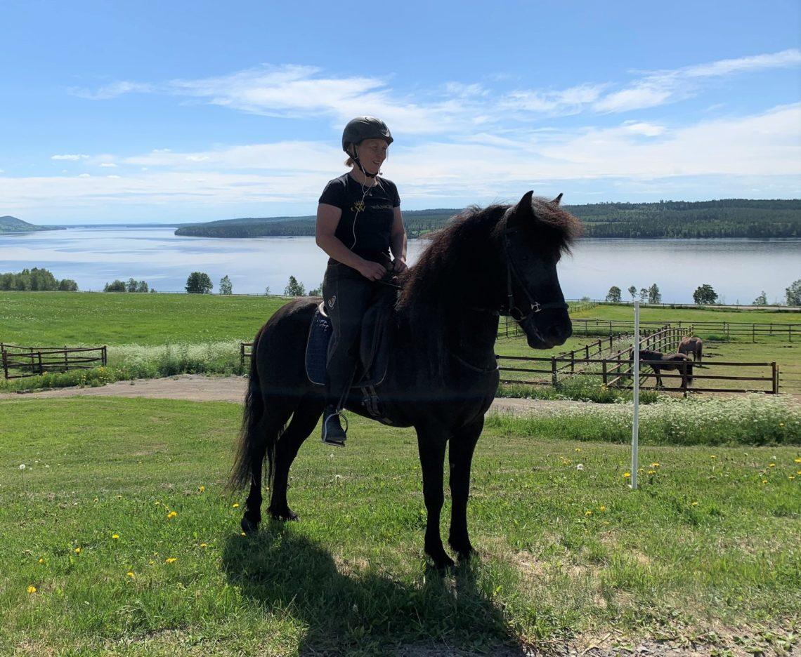 Kvinna i t-shirt, ridbyxor och hjälm sitter till på en svart islandshäst. Det är sommar och i bakgrunden syns hästhagar, gröna fält och en sjö.