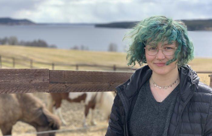 Flicka med grönfärgat kort lockigt hår som flyger i vinden står framför en hästhage. I bakgrunden syns två islandshästar som äter hö från marken.