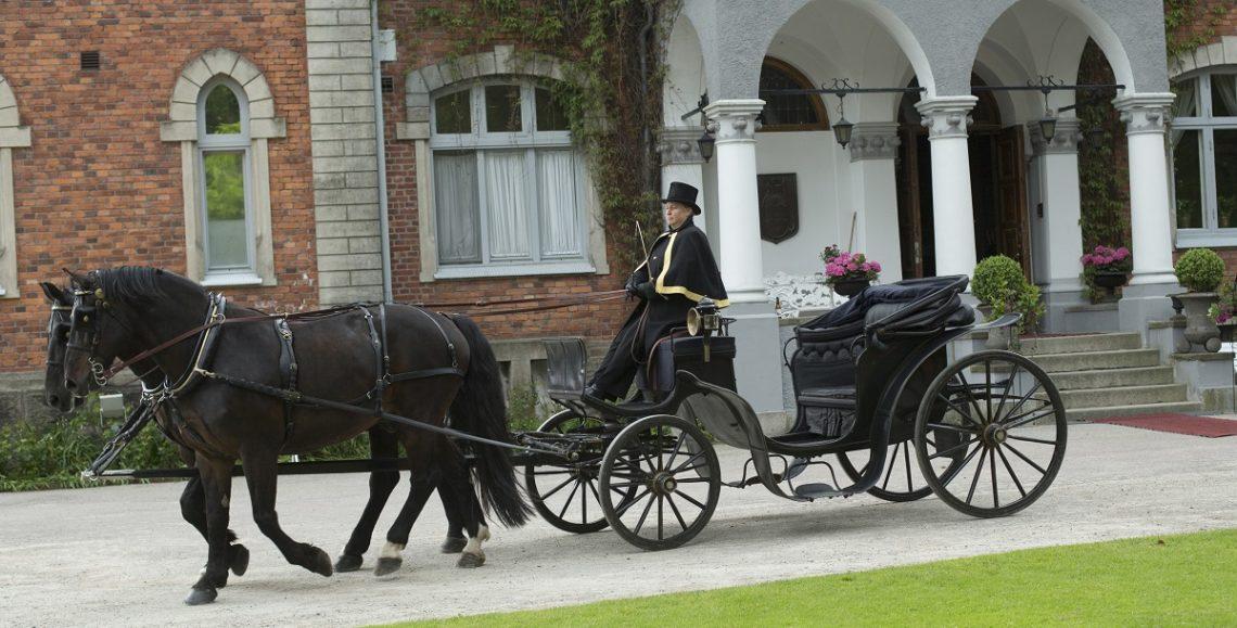 Svarta hästar i par spända framför öppen vagn. Kusken har hatt och körcape. I bakgrunden vacker tegelbyggnad och entrétrapp med vita pelare