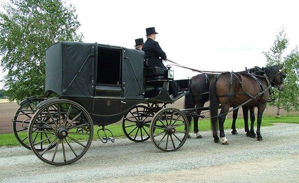 Svart täckt vagn med två kuskar på kuskbocken iförda svarta höga hattar. Halvblodshästar i par är spända framför