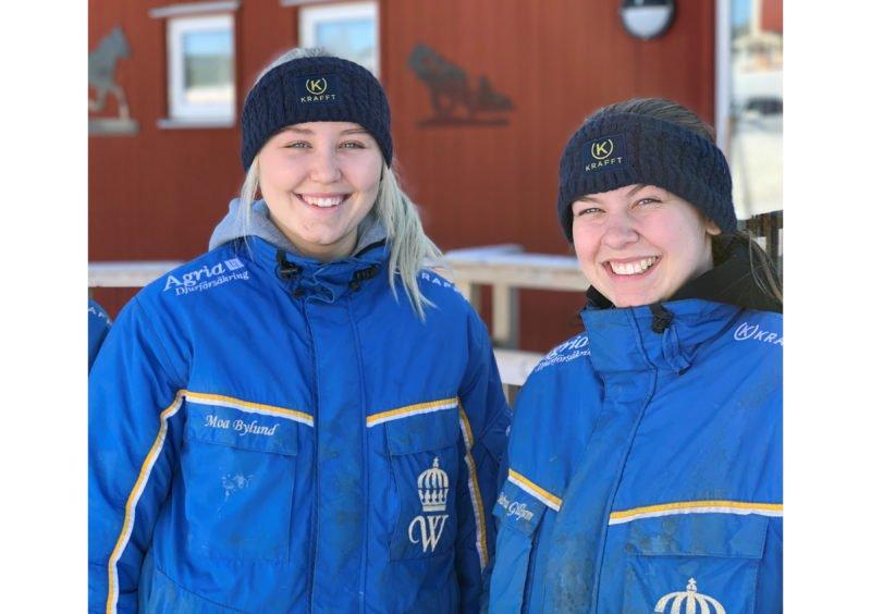 Två glada tjejer iklädda pannband från KRAFFT och jackor med Wångens sigill står framför en byggnad med röd träpanel