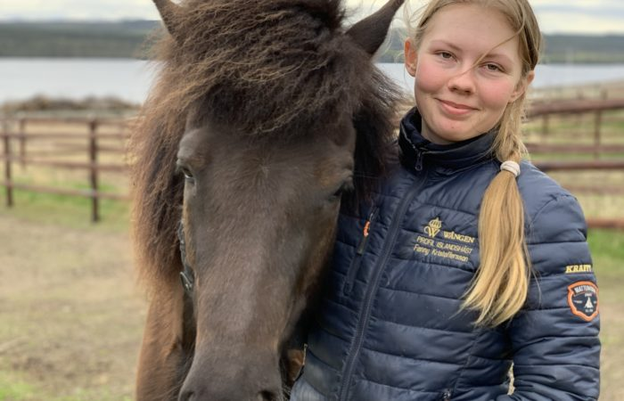 Bleksvart islandshäst i hage utan grimma står bredvid ung kvinna i jacka med Wångenemblem på och sitt namn broderat på bröstet. Hon är blond och har långt hår i tofs och ler lite