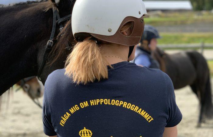 Kvinna i vit travhjälm står med ryggen mot kameran. På hennes t-shirt står det Fråga mig om hippologprogrammet och Wångens logotyp. I bakgrunden syns en ridplan och del av en travhästs huvud och lite längre bort en islandshäst.