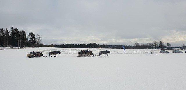 På håll ser man två slädekipage ta sig fram genom vitt snötäckt landskap