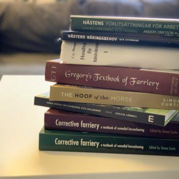 Åtta böcker på hög på ett bord. Titlarna visar att det är böcker om hästhållning och hovvård