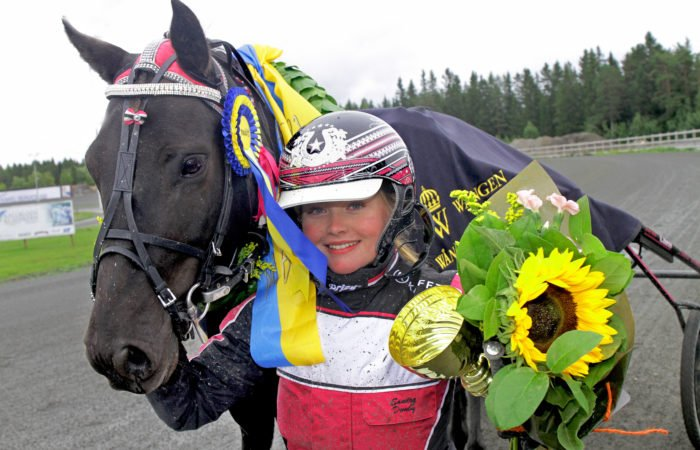 Svart ponny med prisrosett hålls av kusk med pokal och blombukett i handen