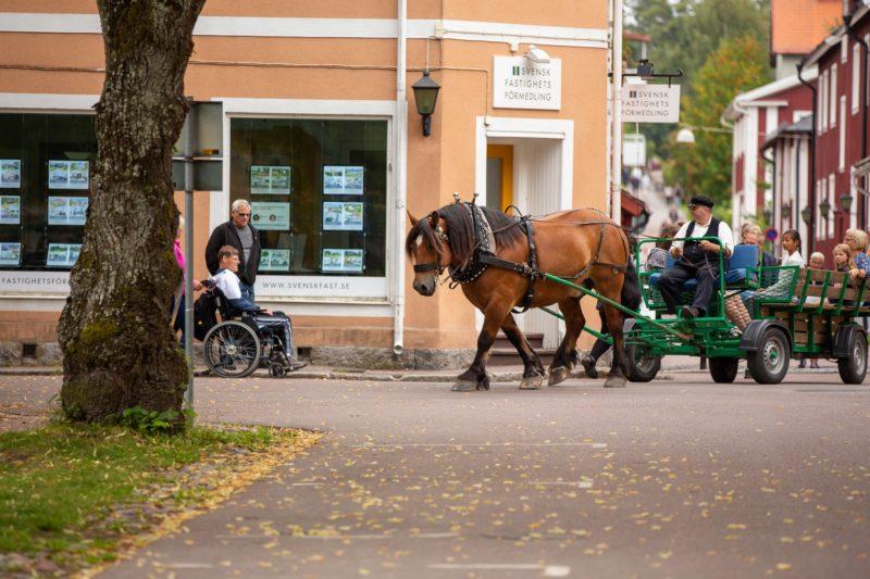 Man i vit skjorta och svart väst och keps kör häst på gata i stan. I vagnen sitter barn och bakom syns gamla röda trähus.