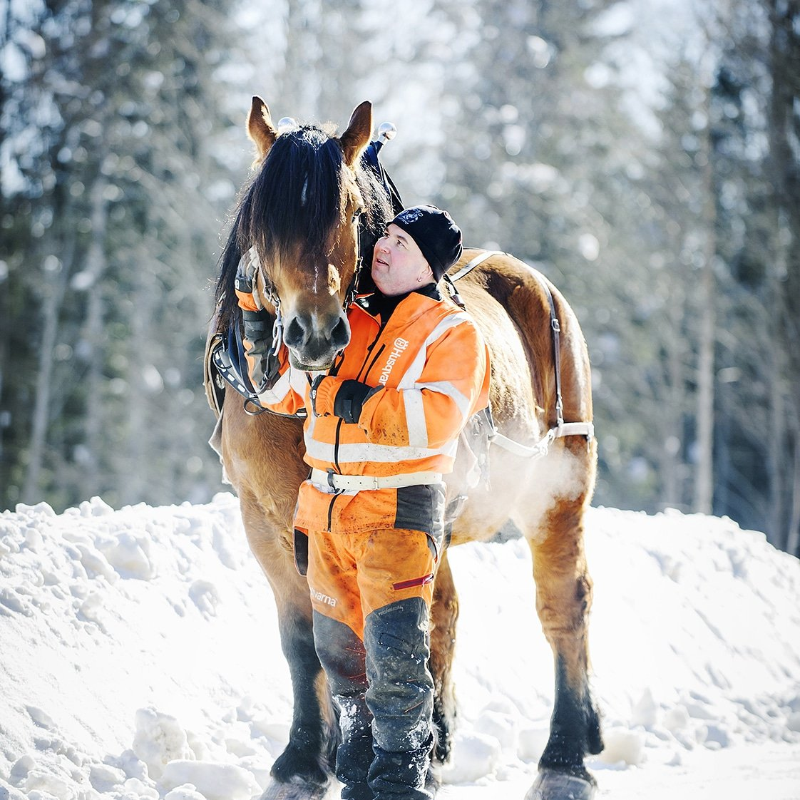 Man i varselkläder och mössa står bredvid och håller i sin häst i ett snöigt skogslandskap. Det är kallt, utandningsluften syns från hästen