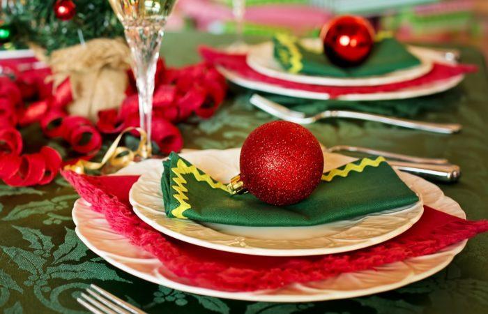 På grön duk är det dukat med tallrikar gröna och röda servetter och en glittrig röd julkula. Foten på ett högt glas syns. Nu är det dukat för julcatering