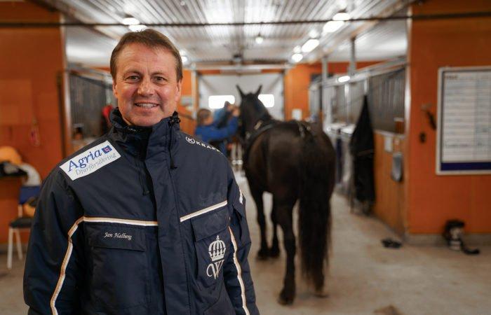 Jan Halberg tränare i stallet i mörkblått travställ med Wångens sigill på står i en stallgång under campkontroll. I bakgrunden skymtar en häst och en hästskötare.