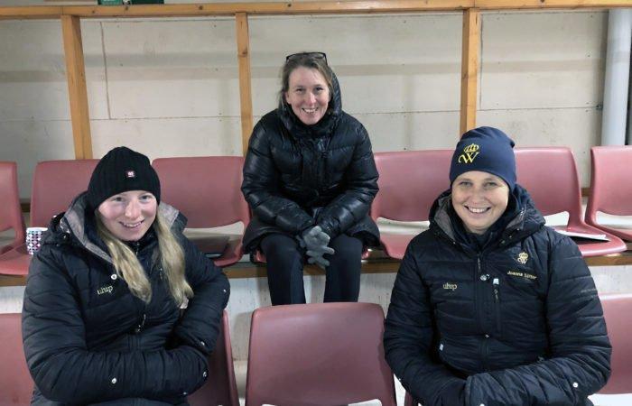 Tre leende kvinnor sitter på läktaren i ridhuset på Wången för att symbolisera den digitala läktaren till clinicen Tölt & pass – steg för steg