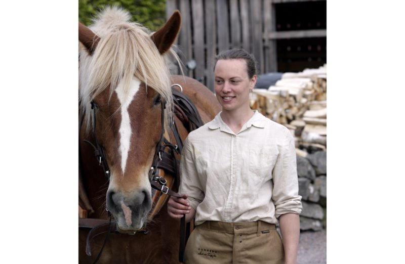 Kvinna i vit linneskjorta och beiga byxor står bredvid en selad ardenner. Hästen är en ljusfux med vit bläs. I bakgrunden syns ett omålat skjul och en vedstapel