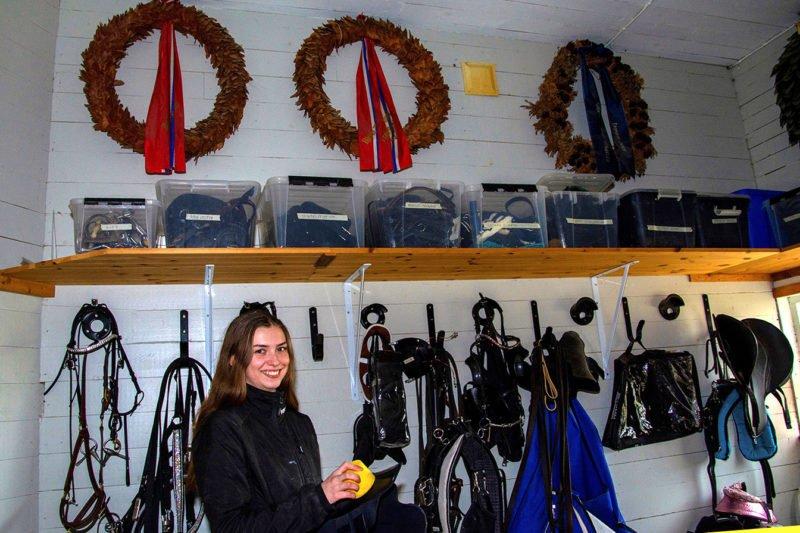 Ailin Berg-Almaas i selkammare med vit liggande panel på väggarna där det hänger segerkransar och seldon