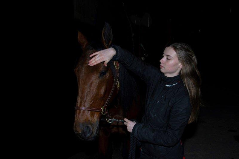 Ung kvinna klappar varmblodstravare i pannan. Hon är klädd i svar och bakgrunden är svart. Bara hästens huvud i träns och flickan syns.