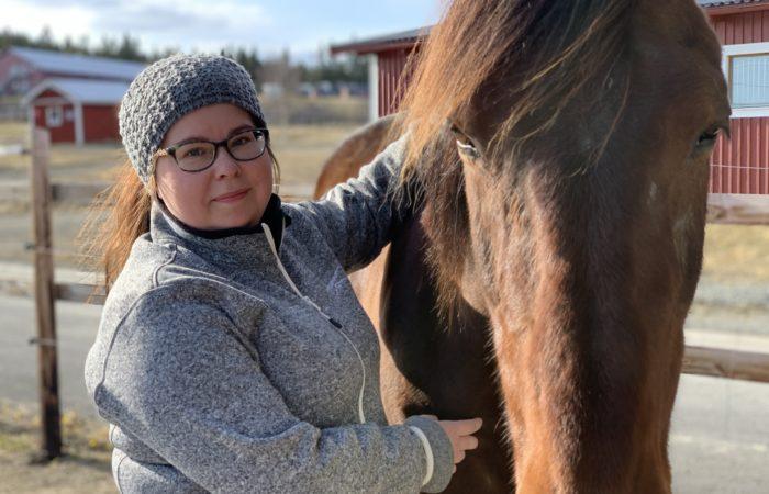 Kvinna står utomhus i hage tillsammans med en varmblodstravare