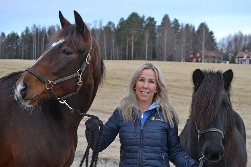 Kvinna står utomhus och håller en varmblodstravare i ena handen och en svart islandshäst i andra.
