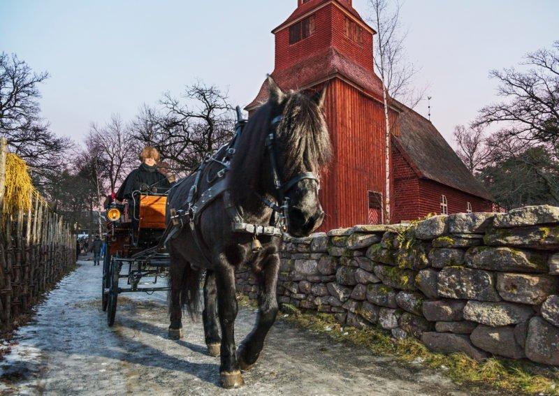 Svart nordsvensk drar vagn framför röd träkyrka.