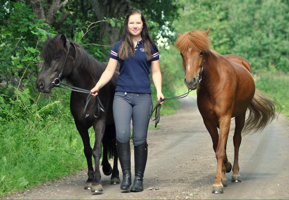 Idrottspsykolog Elise LIndman leder två islandshästar på en grusväg genom en grön skog